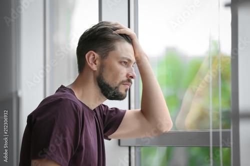 Vászonkép  Lonely depressed man near window at home