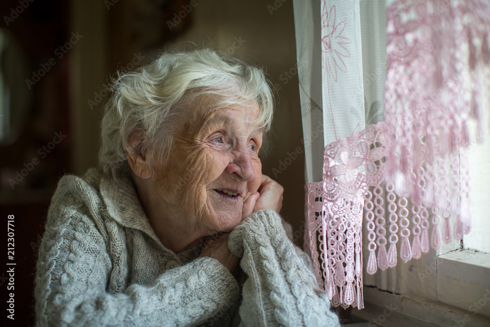 Fototapety, obrazy: A gray-haired elderly woman sits and looks out the window.