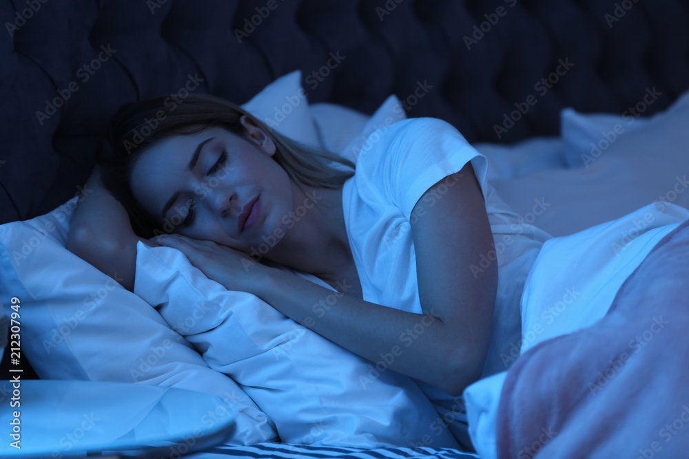 Fototapeta Young woman sleeping in bed at night. Sleeping time