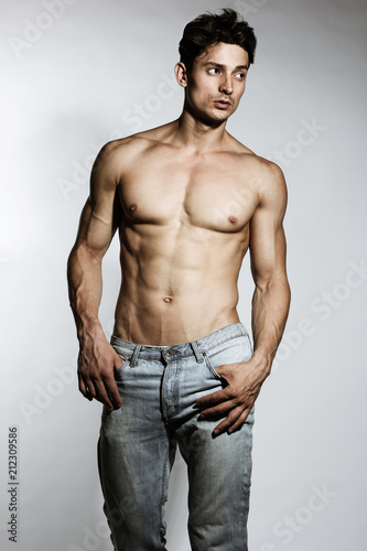 Deurstickers Akt Male model with perfect body in jeans posing over grey background. Close-up. Studio shot.