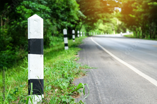 Foto  Black and white milestones with green grass roadside, Trees roadside in background