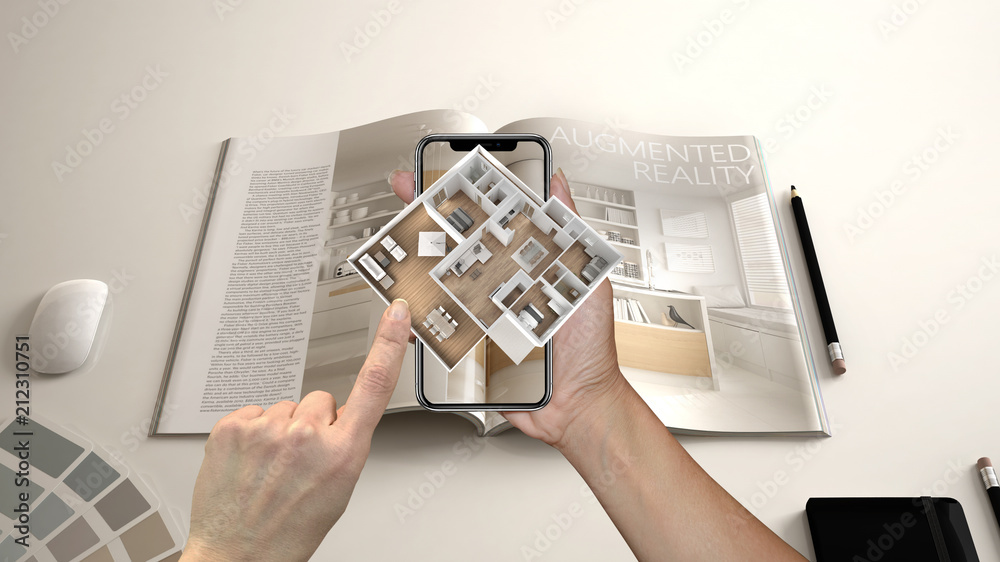 Fototapeta Augmented reality concept. Hand holding smartphone with AR application used to simulate 3d pop-up interactive house maps to life