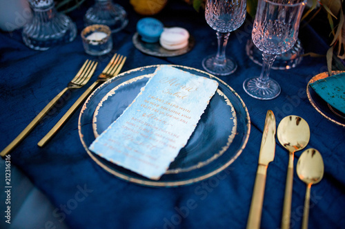 Menu card lies on a blue plate surrounded with golden dinner set
