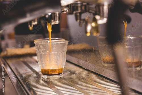 Foto op Aluminium Alcohol espresso coffee shot pouring into piccolo clear grass from a espresso machine in cafe. close-up