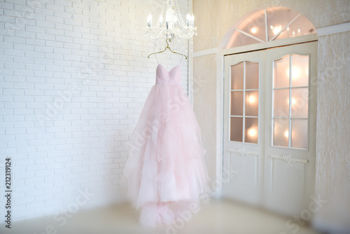 Fotografía  Rich pink wedding dress hangs on a chandelier in a white room