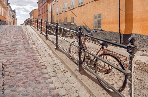 Photo  Bycicle on old street with cobbled stones and colorful historical houses