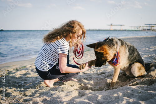 Fototapety, obrazy: Young woman training and playing with her German shepherd dog outdoor on the beach