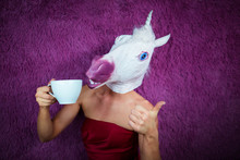Funny Girl Unicorn Drinks Tea And Shows Thumbs Up Gesture. Freaky Young Woman In Comical Mask Stands On The Purple Background. Portrait Of Unusual Lady In Red Dress.