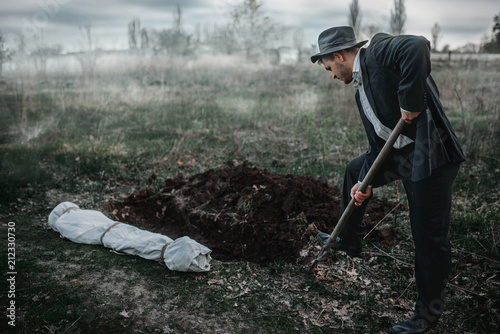 Killer is digging a grave for the victim in forest Canvas Print