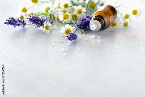 Fototapeta Globulis im Fläschchen mit Lavendel und Kamillenblüten auf lackiertem weißen Holz obraz