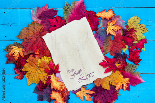 Fotografie, Obraz  Hope, Faith, Love on parchment paper with colorful autumn leaves border on rusti
