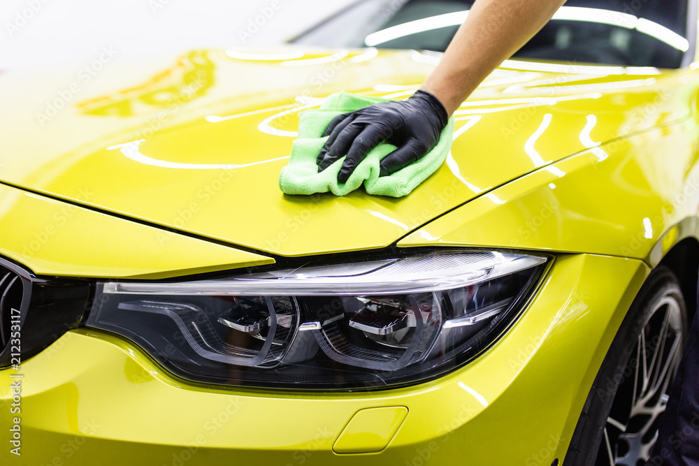 Fototapety, obrazy: A man cleaning car with microfiber cloth, car detailing (or valeting) concept. Selective focus.