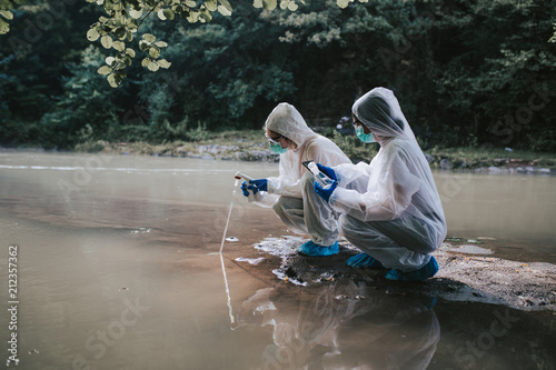 Fotografía  Two scientists in protective suits taking water samples from the river