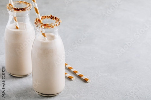 Staande foto Milkshake Vanilla milkshake in glass bottles on a gray background