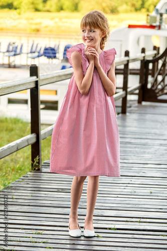 Slender Teen Girl Is Wearing Summer Cool Dress In Red Stripesoutdoors Lovely Child Looks Away Smiles Full Length Pretty Kid Standing Resting