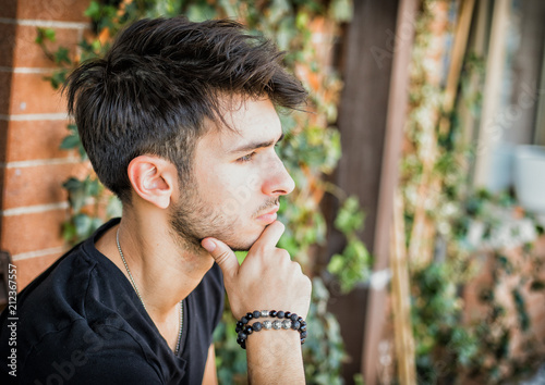 Fotografija  Handsome dark haired, green eyed young man sitting in a balcony, looking out at