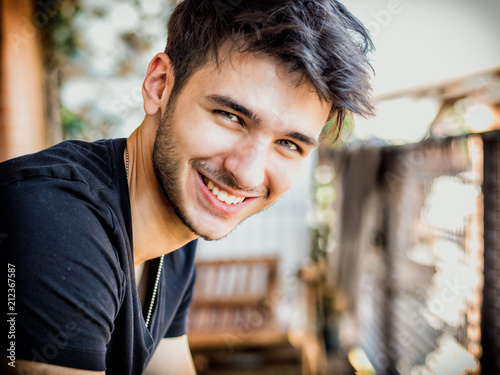 Handsome dark haired, green eyed young man sitting in a balcony, looking at came Fototapeta