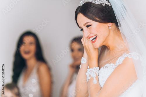 Fotografia Happy bridesmaid hugging the bride in the bedroom in the morning