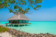 Tropical landscape, water bungalow in a turquoise ocean. Maldives vacation.