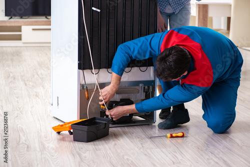 Pinturas sobre lienzo  Man repairing fridge with customer