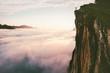 Leinwandbild Motiv Traveler standing on cliff edge mountain top above sunset clouds travel adventure lifestyle summer journey vacations