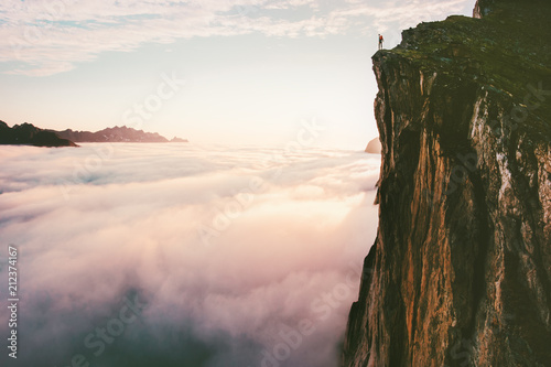 Traveler standing on cliff edge mountain top above sunset clouds travel adventur Canvas Print