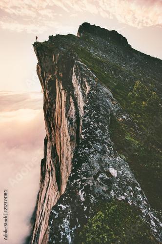 Man standing on cliff edge mountain ridge above sunset clouds travel adventure l Canvas Print