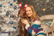 cute girl in sweater hugs her brown dog on white Christmas tree and black wall