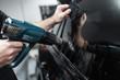 Car tinting - Worker applying tinting foil on car window.