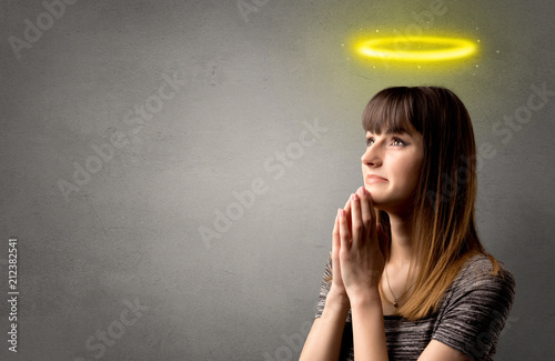 Obraz na płótnie Young woman praying on a grey background with a shiny yellow halo above her head
