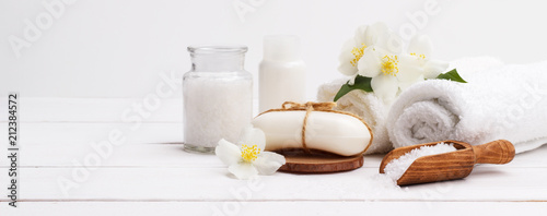 Spa setting and health care items,jasmin aromatic soap,body oil,bath salt,milk,massage stones and towels, on wooden board