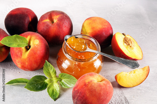 Peach vanilla jam with fresh peaches on table.