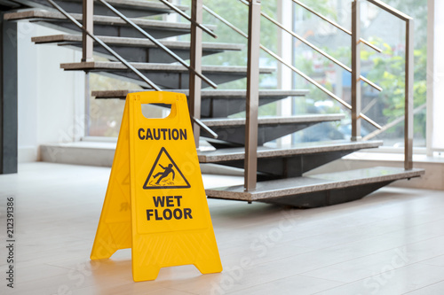 Leinwand Poster Safety sign with phrase Caution wet floor near stairs