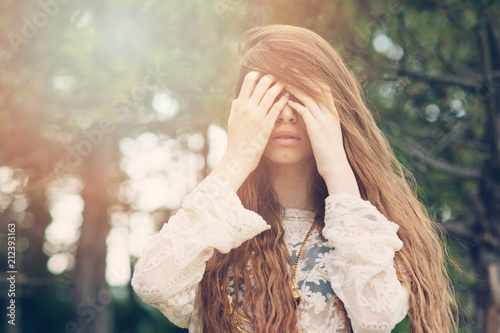 Fényképezés  Shy or emotional woman with long blonde hair outdoors in forest on sunny day