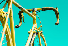Partial View Of A Yellow Painted Road Bike Against Green Background