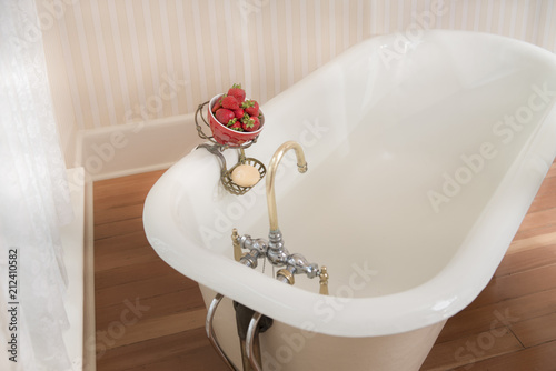 Fotografie, Obraz  Antique bathtub with soap and strawberries in brass hanger on the edge