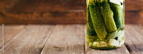 Salted Cucumbers in a Glass Jar on a Wooden Table, Canned, Vegetable Harvesting