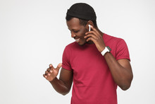 Young Handsome African American Man In Red T Shirt, Wireless Headphones And Smart Watches Listening To His Favourite Song, Dancing, Smiling With Closed Eyes