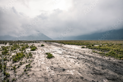 Poster Donkergrijs muddy road through grassland with mountain as background