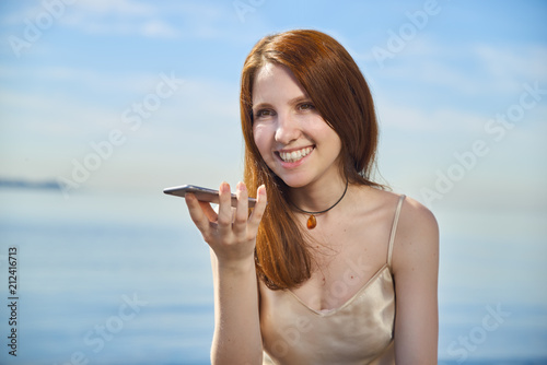 Portrait of a girl using the voice recognition of the phone. Canvas Print