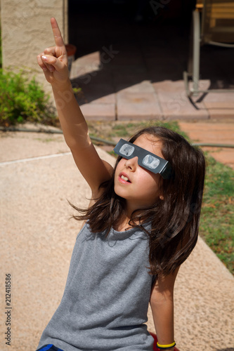 Young Girl Pointing To the Sky While Wearing Eclipse Glasses On a Bright Day