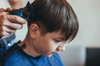 Hairdresser does a haircut with clipper for the boy
