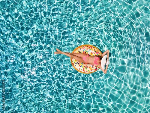 Junge Frau mit Sonnenhut enstpannt auf einer Donut förmigen Luftmatratze über bl Canvas Print