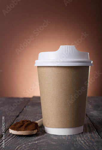 Fotografie, Obraz  Special container for take-away coffee, ground coffee into spoon on table