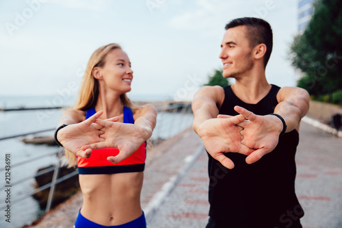 Fotografiet  Happy man and smiling woman doing stretching exercises for arms during workout on the quay
