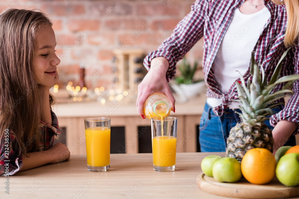 Fototapeta child health and development. useful and tasty drink. vitamin orange juice for balanced nutrition. family healthy lifestyle. mom pouring beverage into glasses