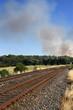 Bedrohliche Rauchschwaden eines Waldbrandes am Ende eines zweigleisigen Schienenstranges