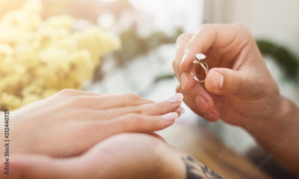 Fototapety, obrazy: Man putting on girl finger engagement ring