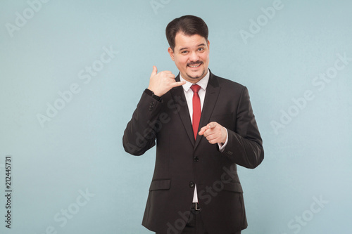 Foto op Plexiglas Artist KB Call center. Businessman showing phone sign and smiling. indoor studio shot. isolated on light blue background. handsome businessman with black suit, red tie and mustache looking at camera.