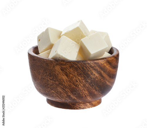 Greek feta cubes in wooden bowl. Diced soft cheese isolated on white background